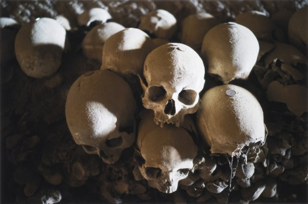 Cluster of skulls with coins on top of their crowns at the Cimitero delle Fontanelle ossuary in Napoli Italy.
