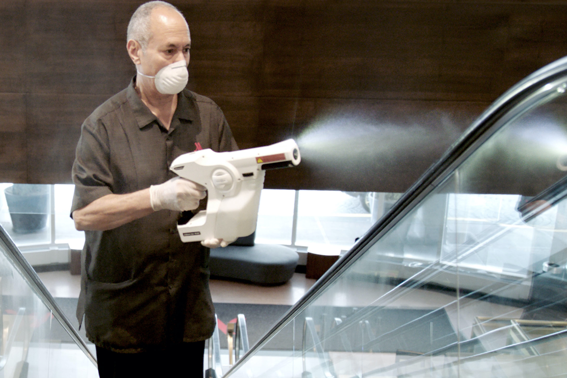 A Marriott associate using an electrostatic sprayer to clean public areas, an example of our elevated cleanliness standards.
