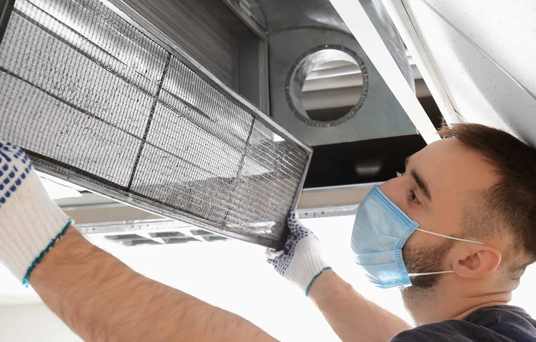 man with face mack cleans air duct