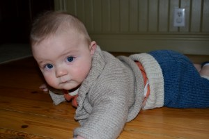 baby cleans floor with sweater