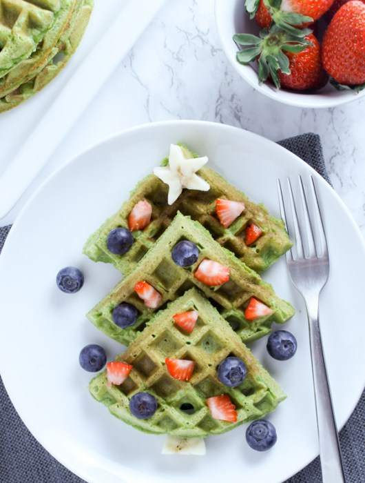 Overhead view of green waffles placed like a Christmas tree with fruit toppings