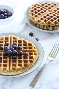 side angle view of waffle with blueberries and syrup