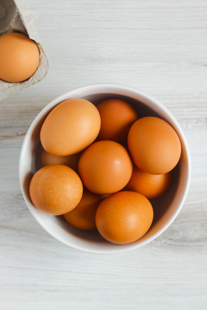 overhead view of brown eggs in white bowl