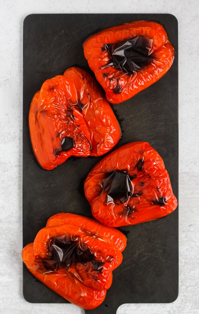 roasted red pepper halves on black cutting board