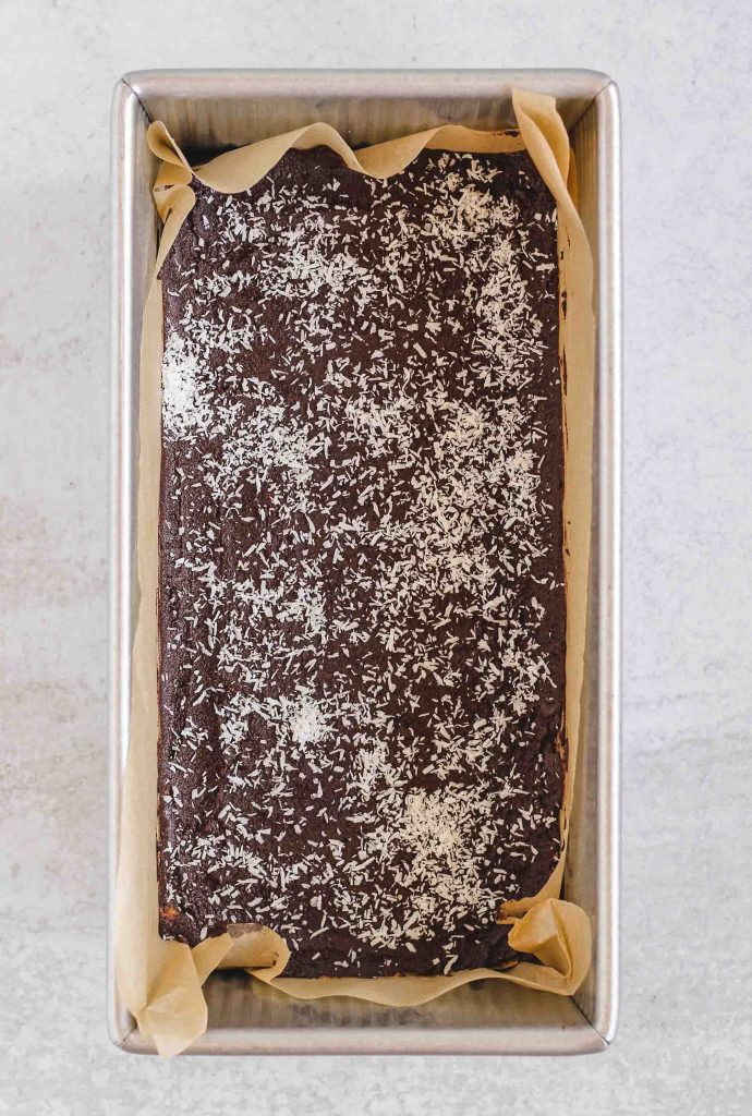 overhead view of bars with chocolate spread and coconut sprinkles in loaf pan