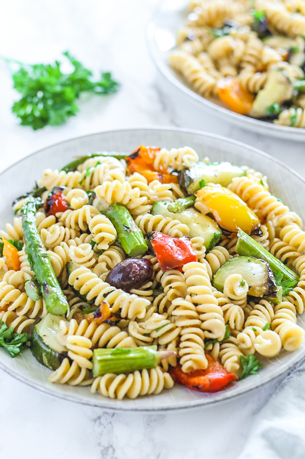 side angle, close-up view of grilled vegetable pasta salad on round plate