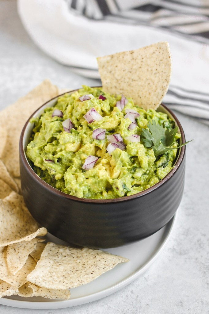 side view of guacamole in a black bowl with a chip sticking out of the quacamole