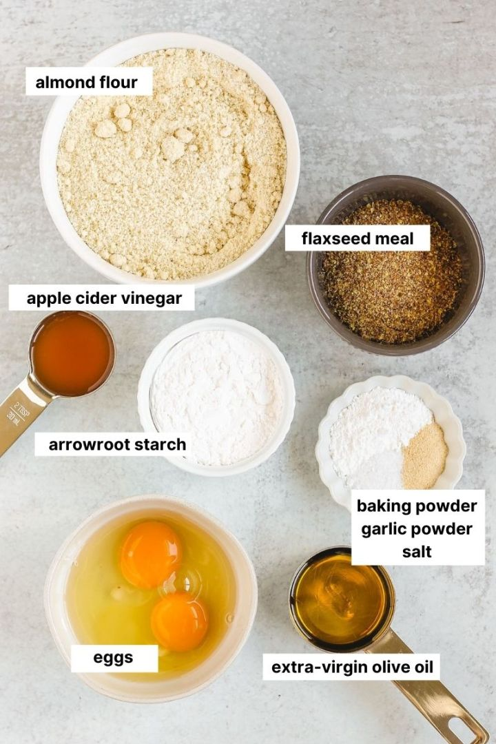 individual ingredients to make almond flour biscuits laid out on a gray counter.