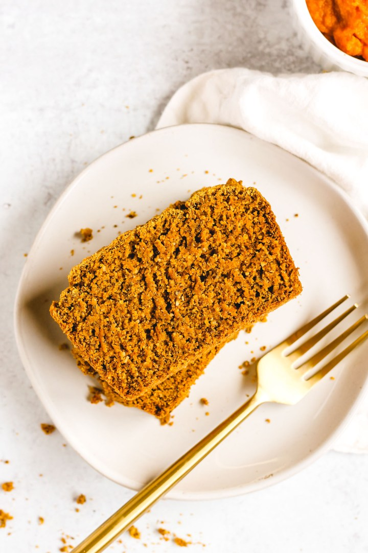 overhead view of a piece of pumpkin bread on a white plate with a gold fork next to the bread