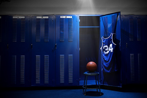 An open locker with a jersey and ball in a authentic basketball locker room. Lots of Copy Space