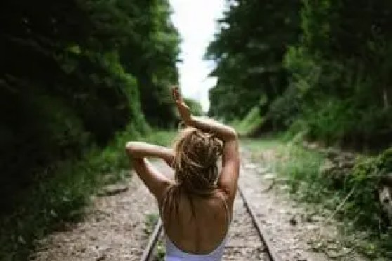 woman standing on empty train track