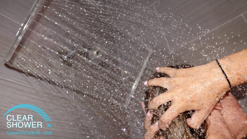 Girl using Clear showerhead in grey bathroom