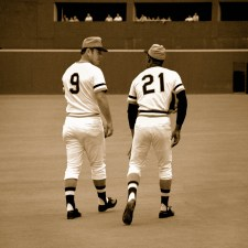 Roberto Clemente walks and talks with Bill Mazeroski.