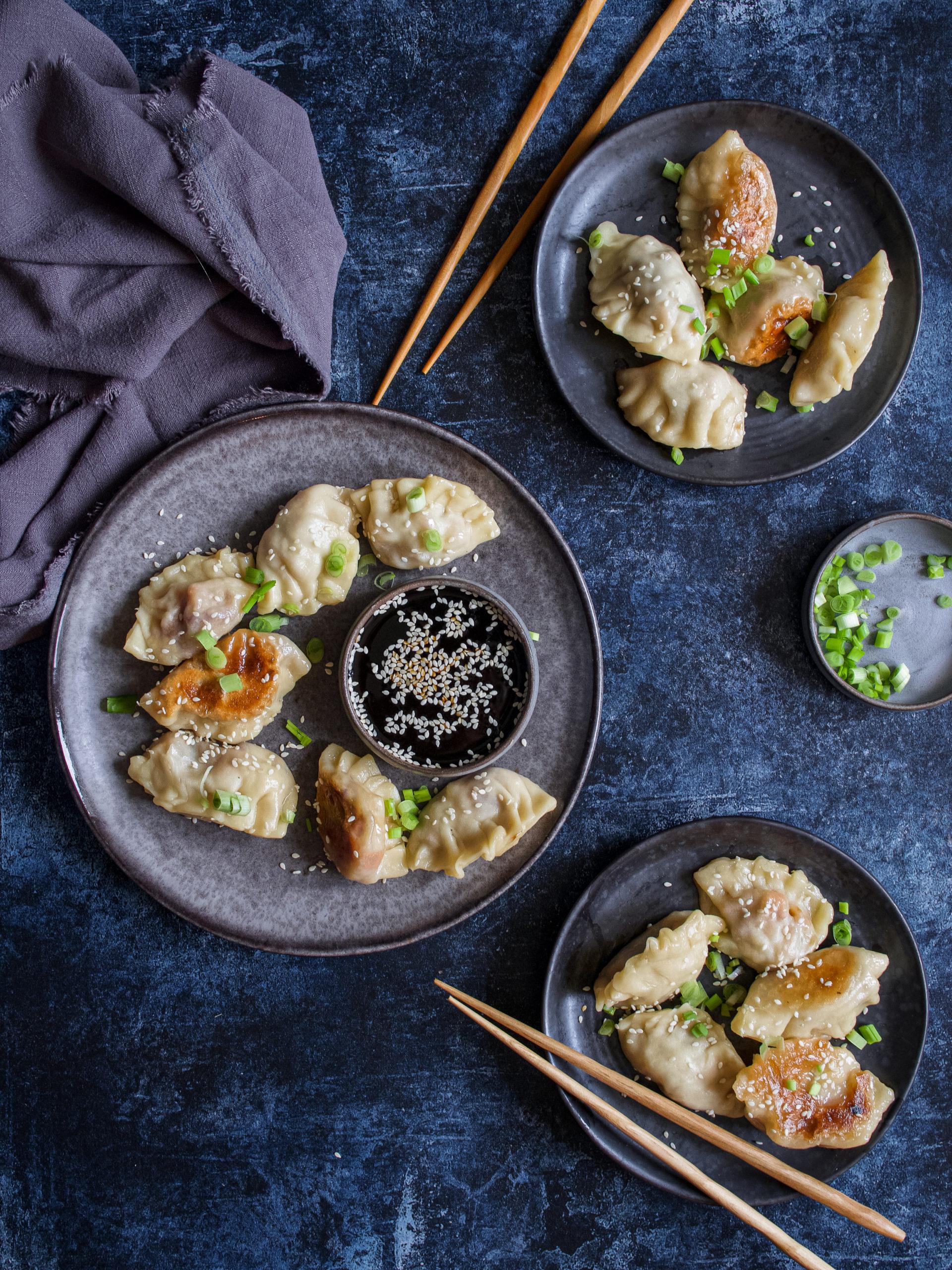 des raviolis japonais avec de la sauce soja, de la ciboule et du sésame