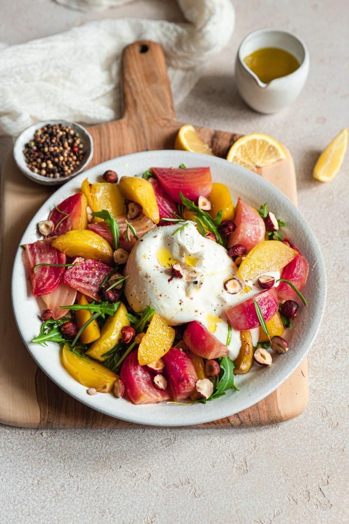 fond clair, planche en bois et dessus une assiette avec une boule de burrata au centre, des betteraves jaunes et roses et des noisettes, et quelques feuilles de roquette