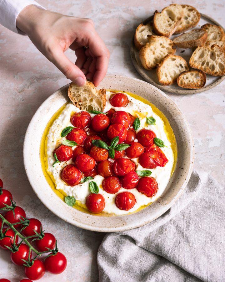 dip de feta et yaourt grec avec tomates cerises rôties et pain grillé qu'une main trempe dans le dip