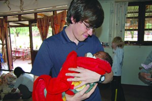 Britton McCaskill holds a baby in Tanzania, Africa, where he and a group of undergraduates in a Creative Inquiry class with Professor Delphine Dean traveled to help build a low-cost alternative to neonatal incubators.