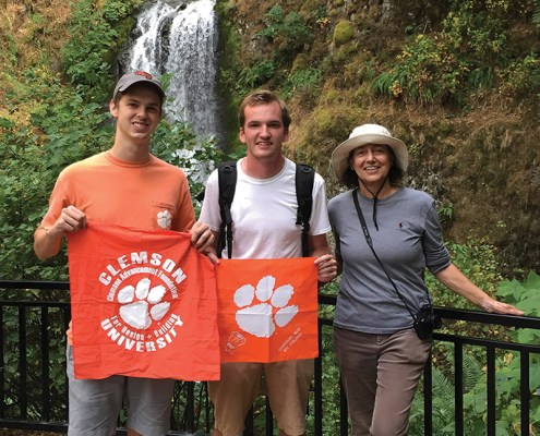 Oregon Adam Rourke '14, Dawson Powers '11 and Annemarie Havenga Jacques '76, M '81 show their Tiger Rags at Multnomah Falls, along the Columbia River Gorge.