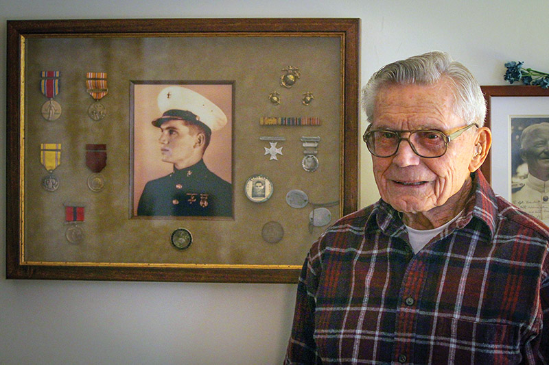 "Retired U.S. Marine Staff Sgt. Robert A. Henderson, 95, a Pearl Harbor survivor, poses next to his medals and a photo of himself from the era, Feb. 21, 2015. ""Living this long is no accident,"" he said. ""It takes work."" Henderson served more than 50 months in combat during WWII, including at the Battle of Okinawa. ""I was in the first and last battles of the war,"" he said. (Photo by Ken Scar)"