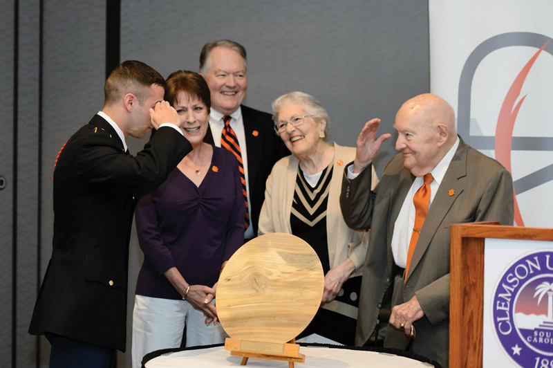 Army ROTC Cadet Matthew Grajewski salutes Wilbur Ginn Jr. after presenting a hand-crafted bowl made from the wood of Clemson trees in appreciation for the Ginn family's gift. Also pictured are Alice Ginn, Will Ginn III and Dotty Ginn.