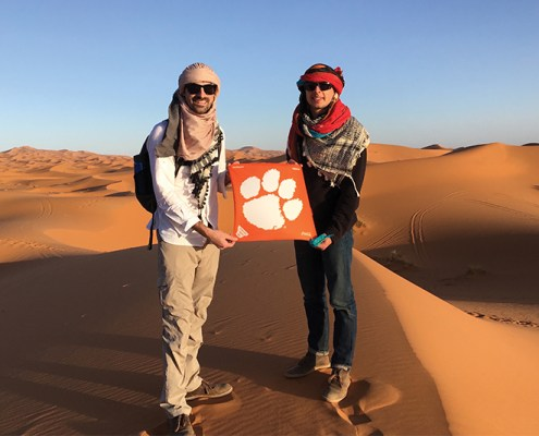 "Zack Geiger '13 and Andy Burns '15 took a three-day tour through the Sahara Desert near Merzouga, Morocco. The pair rode camels into the desert, snapping a picture on the sands with their Tiger Rag on the way to a nomadic campsite. ""It was an exhilarating trip made all the more exciting by angry, spitting camels and our guide quitting on day two after a dispute with the driver. It truly was the trip of a lifetime,"" Burns says."