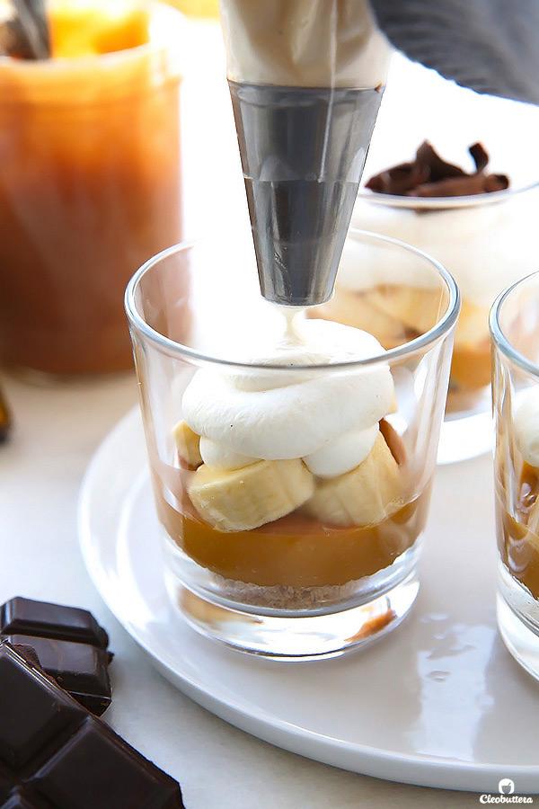 """La tarta de toffee de plátano muy querido hace aún más simple en pequeñas tazas individuales lindo! Con capas de la corteza de galleta digestiva, dulce de leche, rebanadas de plátano y crema batida, esto sin cocción """"pastel"""" es peligrosamente deliciosa y muy fácil de hacer!"""