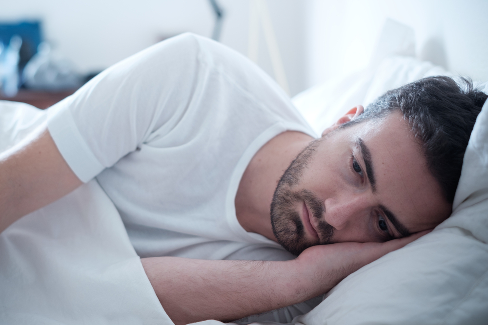 Depressed man lying in his bed and feeling bad