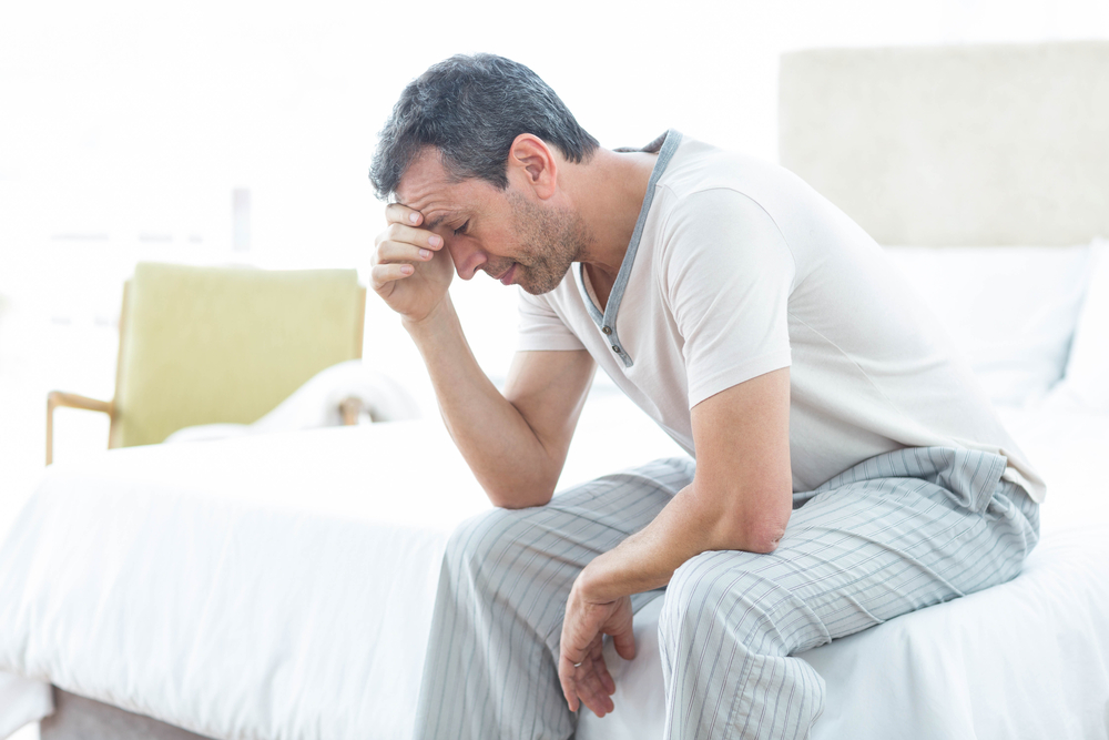 man sitting on bed worried