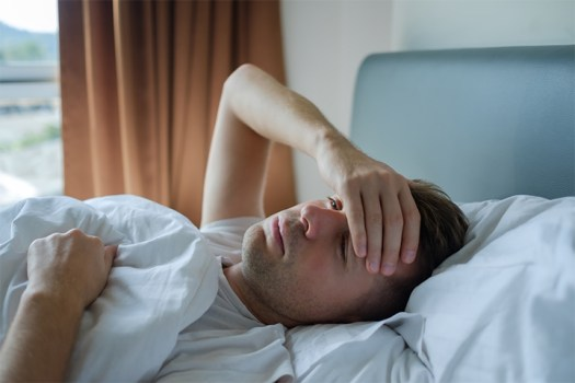 A tired and miserable looking man lying in bed with his hand on his forehead