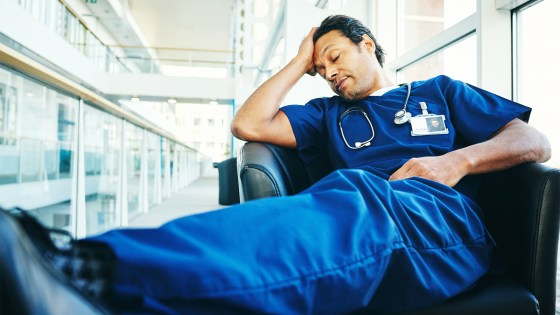 A tired male healthcare worker in dark blue scrubs with closed eyes rests his head on his hand in the doctor's lounge.