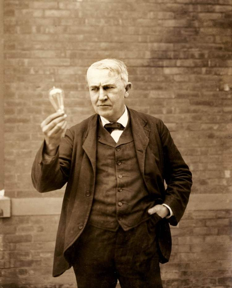 Thomas Edison holding an incandescent lightbulb around 1911