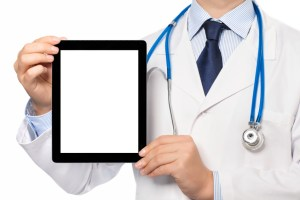 The doctor in a white coat with a stethoscope holding tablet computer with isolated screen