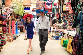 Connie Hanks Photography // ClickyChickCreates.com // engagement couple session, Rosarito, Mexico, mercado, market, colorful, turquoise, blue, gray, wood, wheel, rustic, arches, archways, kiss, sombreros