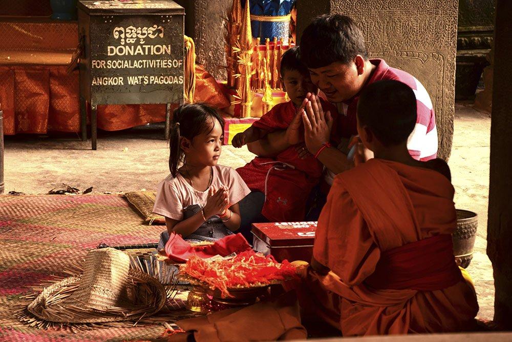 Famiglia in preghiera all'interno di Angkor Wat