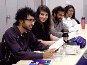 Umair Muhammad signing 'Confronting Injustice' at a meeting of Jane and Finch Action Against Poverty.