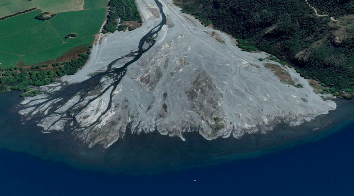 Fig. 4. The Harper River flowing into Lake Coleridge is a good visual analogy of how braided rivers transported sediment from the mountains and deposited it to coastal waters. Over millions of years, as the rivers deposited too much sediment in one place, they changed course to lower-lying areas. Eventually, the land they formed joined into 'megafans', creating what we now call the Canterbury Plains (Image: Google Earth June 2021). Today, braided rivers that have been confined by levees can only deposit these gravels within their confined spaces, eventually building up the riverbed higher than the surrounding land. If the levee breaks during high water flows, an avulsion can happen, leading to widescale flooding with few options to return the water to the river because it's higher than the flooded lands.