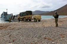 Sailor_directs_a_U.S._Army_light_medium_tactical_vehicle_off_a_landing_craft,_utility._(37285057102)