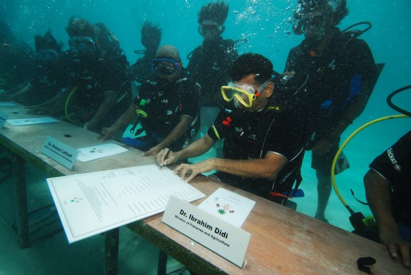 Climate emergency - underwater signing: Maldives Minister of Fisheries and Agriculture Dr Ibrahim Didi signs the declaration of an underwater cabinet meeting, 2009. Photograph by Mohamed Seeneen