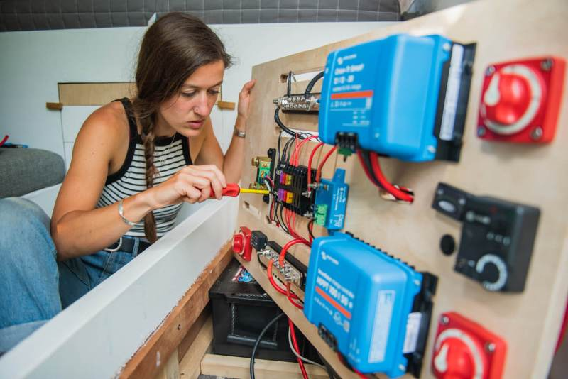 girl wiring a 12V fuse board in a campervan electrical system how to wire a campervan electricsal system board victron