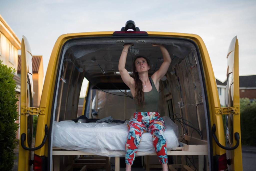 girl glueing autocarpet onto the inside of a campervan conversion to prepare for cladding