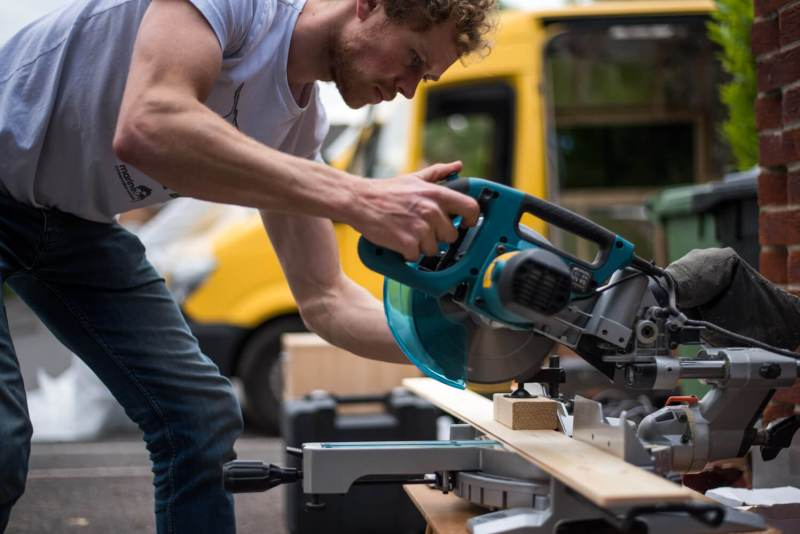 man using a sliding mitre saw for a campervan conversion