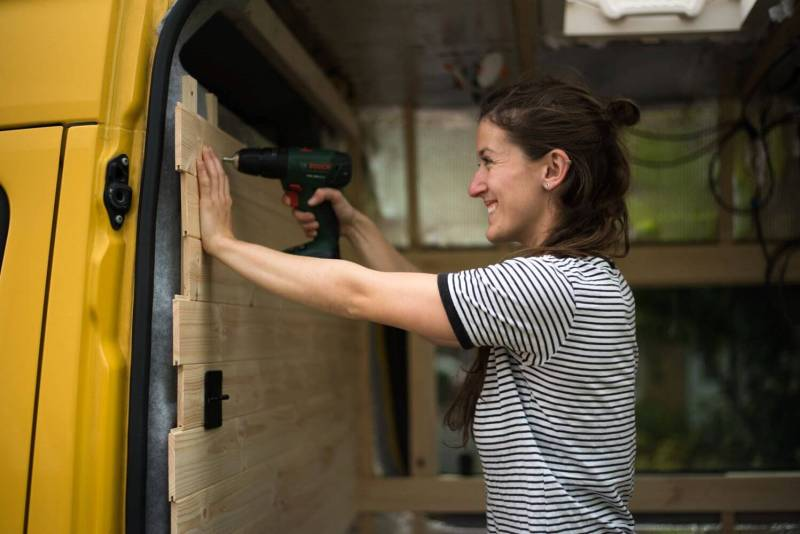 Girl screwing wooden tongue and groove cladding onto a Mercedes Sprinter camper van conversion