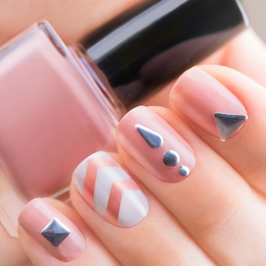 Nail art manicure. Fashion modern beige manicure with metal accessories