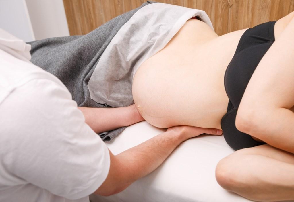 Grávida a receber tratamento osteopático na consulta de osteopatia.