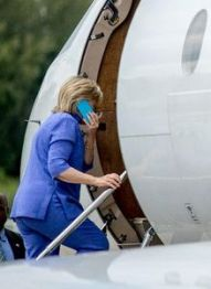 Clinton boards the State Department jet with her BlackBerry, destination unknown. (Credit: Andrew Harnik / The Associated Press)