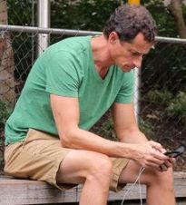 Anthony Weiner, texting in a park. (Credit: Daily Mail)
