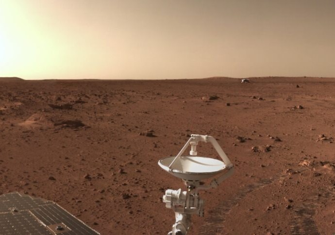 A section of a panorama produced by Zhurong, released June 27, showing comms and solar arrays, roving tracks and the distant landing platform. Credit: CNSA/PEC