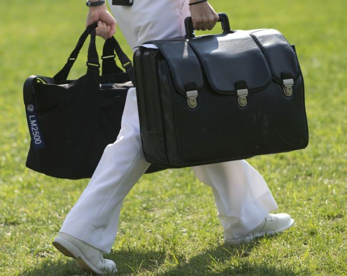 """A White House military aide and member of the US Navy carries a briefcase known as the """"football,"""" containing emergency nuclear weapon codes, as then-President Barack Obama departs from the White House in 2012."""