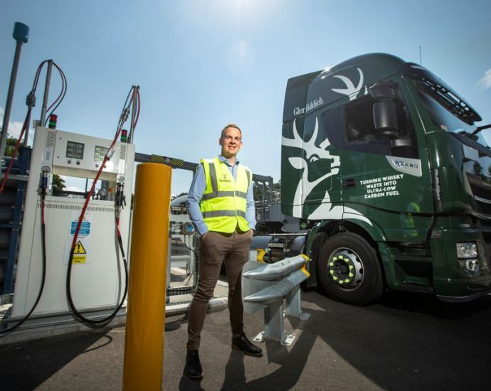 Stuart Watts, a director of Glenfiddich parent company William Grant & Sons, stands by a fuelling station next to their truck, that runs on whiskey-by-product based biogas, in Dufftown, Scotland, Britain in this undated handout obtained July 26, 2021. Courtesy of William Grant & Sons/Handout via REUTERS