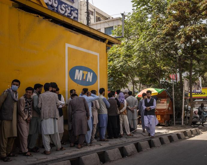 People stood in line outside Azizi bank in Kabul on Sunday, the first day banks reopened in Afghanistan's capital.Credit...Jim Huylebroek for The New York Times